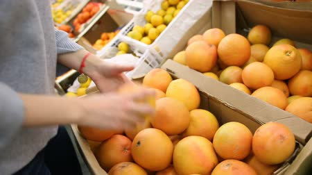 lojas : Young woman chooses orange in the store