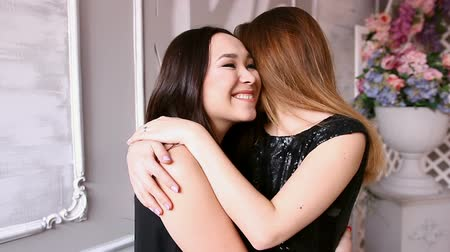 brown dress : Two asian young woman in evening dress hugging