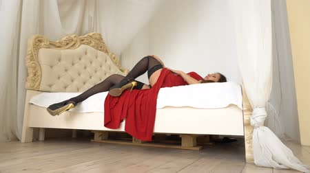 молодые женщины : Beauty brunette woman with attractive body in red dress and black thong possing on bed