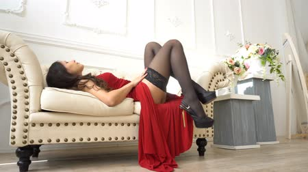 латина : Sexy woman in red dress stroking a leg then lie down on the sofa in sexual pose
