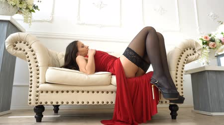 koronka : Sexy woman in red dress stroking a leg then lie down on the sofa in sexual pose