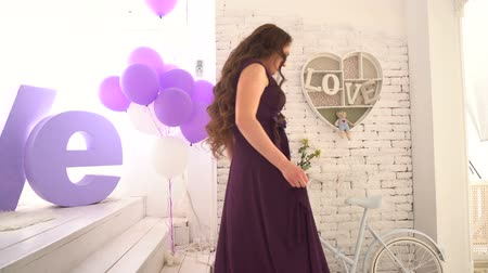 admires : Elegant girl in evening dress standing on a background of large letters love.