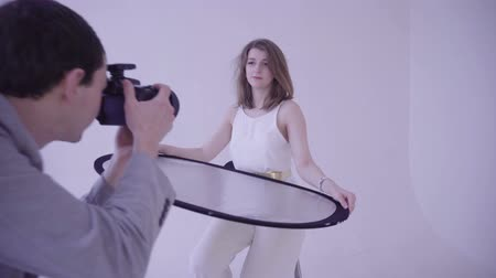 reflektor : The model holds a light reflector on a photo shoot in the studio
