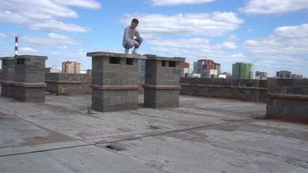 çatı : Young redhead man in a white sweatshirt sits on a brick wall on the roof Stok Video