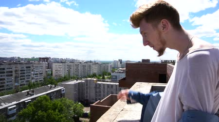 gust of wind : Redhead young man standing on the roof on background of the cityscape and blue sky