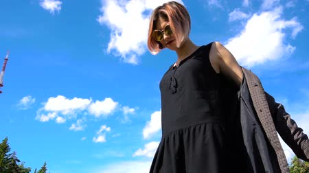 imagem : Young stylish woman take off jacket against blue sky Stock Footage