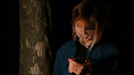sending : Girl uses smartphone at night near tree