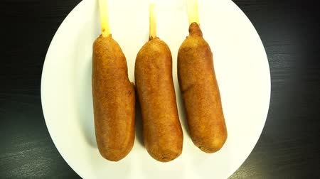 párek v rohlíku : Top view of plate with three corn dogs spinning