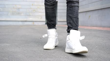kotník : Shot of men legs in sneakers walking on tile road.