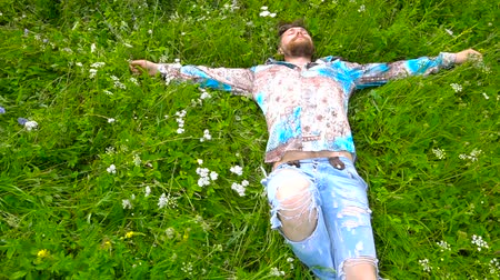 wąsy : Bearded man is lying in a green flower field