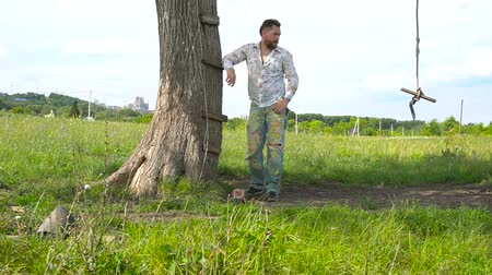 разорвал : Handsome bearded man is leaning on tree in a field Стоковые видеозаписи