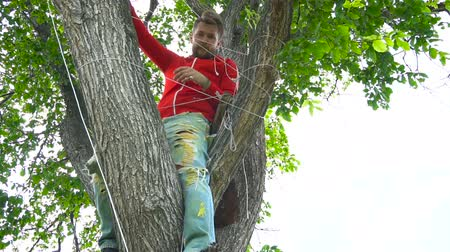 leisureactivity : Cool man in red sitting on a tree