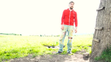 разорвал : Handsome bearded man in red sweatshirt is standing near tree in a field