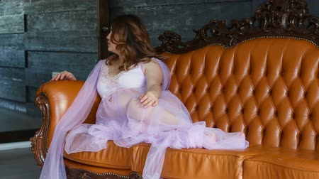 negligee : Young and beautiful pregnant woman straightens his peignoir while sitting on the couch Stock Footage