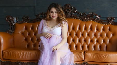 negligee : A young pregnant woman sitting in peignoir on couch Stock Footage
