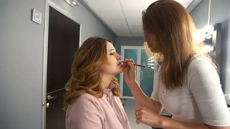 румяна : Makeup artist doing lip contour with pink pencil for girl.