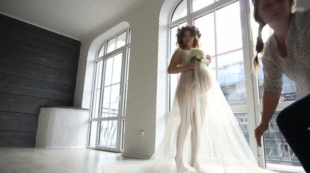 koszorú : girl assistant help to dress peignoir for pregnant bride of wedding dress on studio room