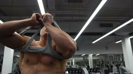 férfias : Bodybuilder man is putting on the tank top after a workout in the gym Stock mozgókép