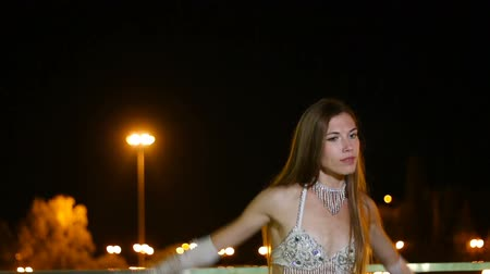 dansçılar : Beautiful girl in oriental costume is dancing fan dance at night outdoor Stok Video