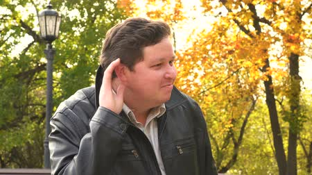 ouvir : Man Listening Secret in Autumn Park, outdoor
