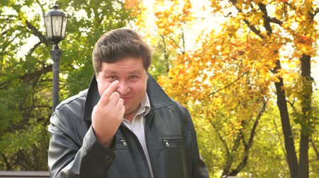 beckoning : Smiling fat man showing come closer gesture with finger in autumn park Stock Footage