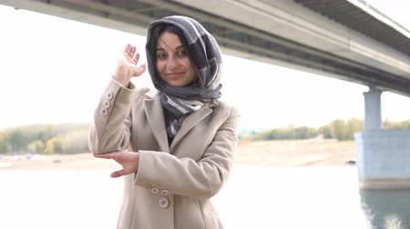 know : Beautiful Muslim girl raising hand
