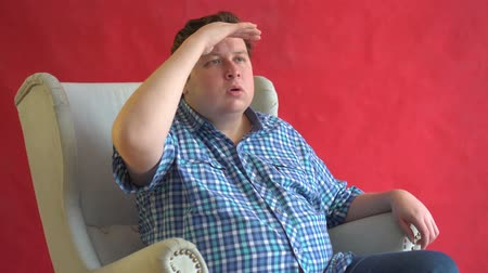 looking far away : A young man in a plaid shirt looks into the distance with his hand to his face against red background Stock Footage