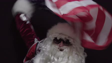 usa independence day : Santa claus waving a US flag against black background - the concept of Christmas or Independence Day USA Stock Footage