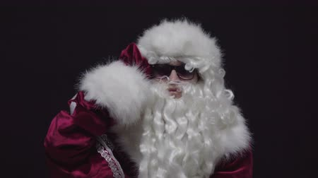 looking far away : Santa Claus in Sunglasses Looking Away and Seeking Good Children against black background.