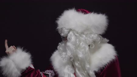 here : Santa claus showing come closer gesture with finger against black background Stock Footage