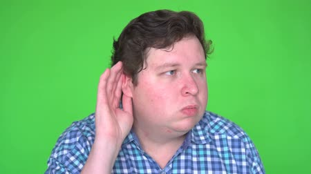 listens : Young man eavesdropping and making funny facial expression on green screen