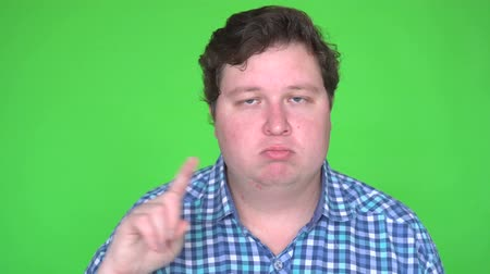 caution sign : Man in shirt making NO gesture on green screen chroma key.