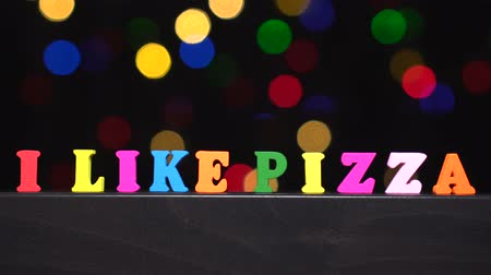 eu : Colorful words i like pizza from multi-colored wooden letters in front of abstract blurred lights bokeh background Vídeos