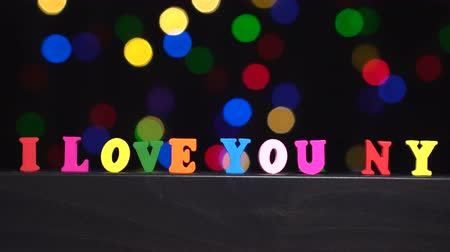 я тебя люблю : Colorful words i love you NY from multi-colored wooden letters in front of abstract blurred lights bokeh background Стоковые видеозаписи
