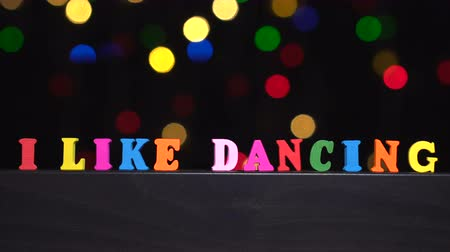 eu : Colorful words i like dancing from multi-colored wooden letters in front of abstract blurred lights bokeh background
