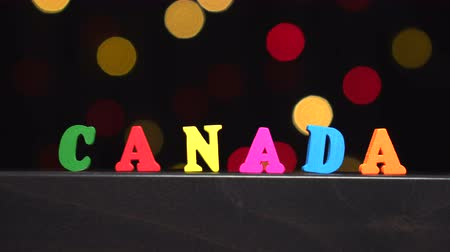 słowa : Colorful word Canada from multi-colored wooden letters in front of abstract blurred lights bokeh background