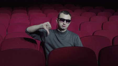 lugares sentados : Single man sitting in comfortable red chairs in dark cinema theater and showing thumbs down