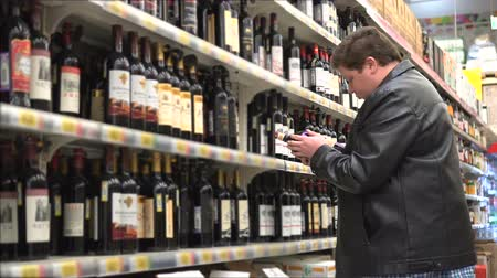 realization : Young fat man chooses wine in a store or supermarket