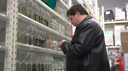 столовые приборы : Man shopping in supermarket choosing wineglass
