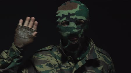 without face : Portrait of soldier in camouflage and a balaclava waving at the camera