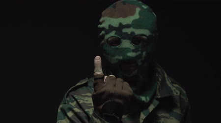 without face : Portrait of soldier in camouflage and a military mask inviting for someone or something.