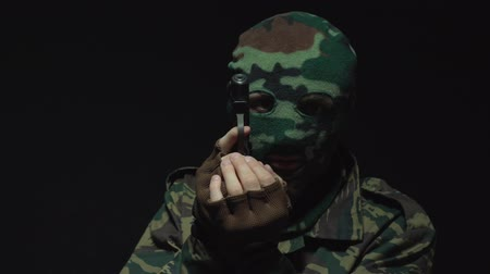 guarda costas : Angry soldier in camouflage and military mask holding gun against an black background
