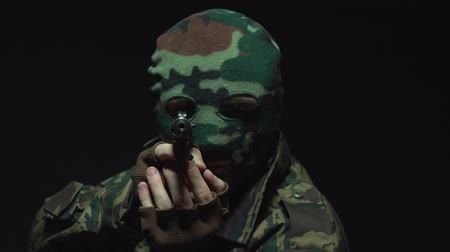 герой : Angry soldier in camouflage and military mask holding gun against an black background