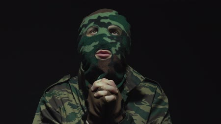 without face : Portrait of soldier in camouflage and military mask is praying on black background