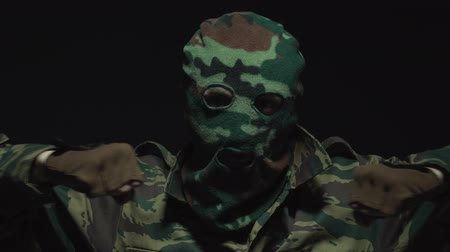 without face : A soldier in camouflage and a military mask preparing for battle Stock Footage