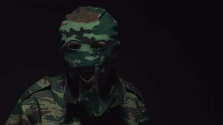 without face : soldier in camouflage and military mask looks at camera on black background