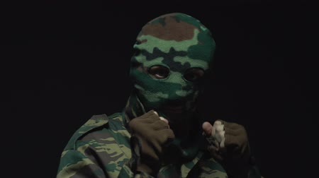 солдат : A soldier in camouflage and a military mask preparing for battle Стоковые видеозаписи