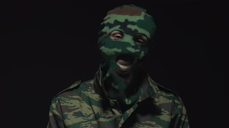 without face : Soldier in camouflage and military mask smiling and looking at camera on black background Stock Footage