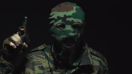 without face : Soldier in camouflage and a military mask holds a gun