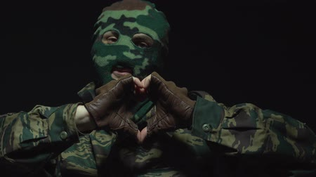 balaclava : Soldier in camouflage and a military mask making a heart with hands, isolated on black Stock Footage